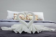 towel folded in swan shape on bed sheet - stock photo