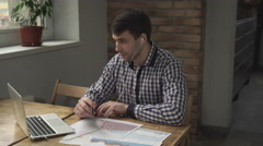 Manager discussing online figures for the month on the table are charts and Stock Footage