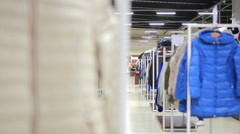 Various clothes on hangers in a store. slider shot - stock footage