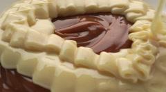 Pouring creamy condensed milk over chocolate cream. Macro shot - stock footage