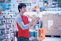 Man in using handheld computer in shop - stock photo