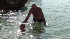 Granddad and his grandson play in the sea - stock footage