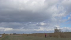 Tourist is Walking Away by Dry Field Thunderclouds Are Upon the Field Dry Grass Stock Footage