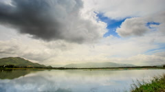 Motion of White Grey Clouds over Tranquil River Hills Stock Footage