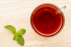 Glass cup of tea with mint on the bright wooden table Stock Photos