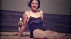 1939: Women in blue bathing suit chews gum winks and smiles on beach. TRYON, NC Stock Footage