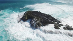 Aerial shot of ocean waves and cliff - waves washing up on a rock, Hawaii Arkistovideo