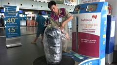 Vietnam transportation, luggage wrapping service at Hanoi airport - stock footage