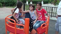 Small boy and three girls on a little go-round Stock Footage