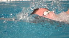 Young handsome man swims in the swimming pool. Close up slow motion shot - stock footage