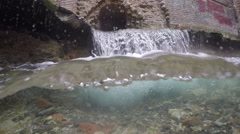 Underwater split: waterfall flowing from old destroyed house. Stock Footage