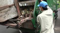 Trash collection, garbage truck, worker wearing hygienic mask, Hanoi, Vietnam Stock Footage