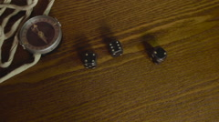 Seaman plays dice on old wooden table with a compass Stock Footage