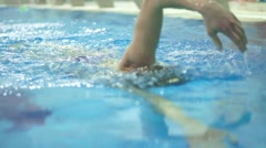 Man swimming in swimming pool towards the camera. Slow motion video - stock footage