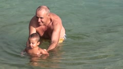 Zoom out granddad and his grandson have fun in the sea - stock footage