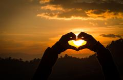 Silhouettes hand heart shaped with sunsets. - stock photo