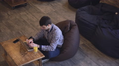 Manager sitting in coworking and works for a laptop on the table is orange juice Stock Footage