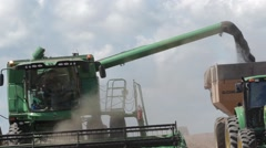 Big combine harvesting and discharging in the same time - stock footage