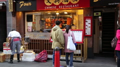 Asian couple looking at menu at Chinese restaurant, Chinatown, London, UK - stock footage