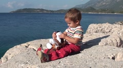 Child sits at the sea and plays with a soft toy Stock Footage