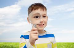 happy little boy looking through magnifying glass - stock photo