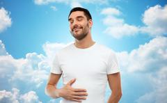 Happy full man touching tummy over blue sky Stock Photos
