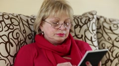 Woman reads a book. Senior woman sits on a sofa and reads electronic book Stock Footage
