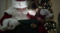Santa and little girl look into magical bag of toys Stock Footage