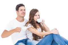 Young couple sitting on floor drinking coffee - stock photo