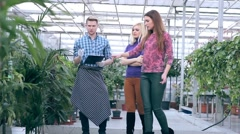 Florist communicating with customers in greenhouse - stock footage