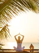 Young woman practicing yoga on the beach at sunset Stock Photos