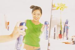 Girl spraying hairspray - stock photo