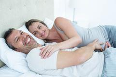 Expecting couple lying on bed and chatting - stock photo