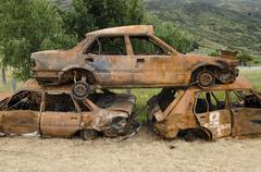 Stack of three rusty car wrecks car cementery South Island New Zealand Oceania - stock photo