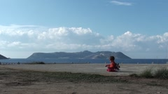 Playing child sitting on cement site 2 Stock Footage