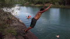 Young black guy jumping into river Stock Footage