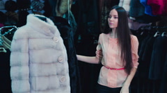 Beautiful brown-haired girl chooses a fur coat in the store. Shopping. Series. Stock Footage