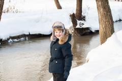 Cute boy walking along a frozen brook on a sunny winter day - stock photo