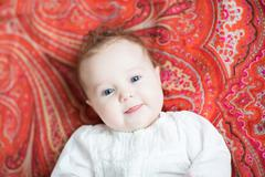 Little baby on a colorful red tulip motif shawl - stock photo