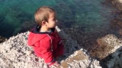 Toddle sitting and watching the sea 2 Stock Footage