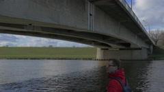Man is Looking at Concrete Old Bridge Water Flows Under Bridge Green Bank Bare Stock Footage