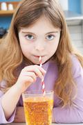 Young Girl Drinking Glass Of Soda Through Straw Stock Photos