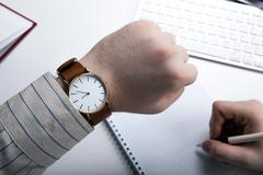 Workplace businessman looks at the clock - stock photo