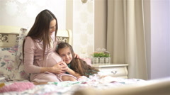 Little girl listening to the belly of his pregnant mother. Slow motion Stock Footage