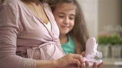 Young pregnant woman and her little daughter play with tiny booties. Slow motion Stock Footage