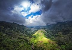 Ray of sun light through clouds under rice terraces in Philippines highlands - stock photo