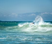 Kitesurfer sportsman makes acrobatic trick on big sea wave - stock photo