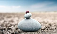 Spiritual and peaceful rock pebble tower on dry deserted land zen like concept Stock Photos