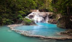 Mountain river stream flows through tropical forest and falls from cascades Stock Photos
