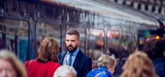 Hipster businessman walking, crowded underground platform, train - stock photo